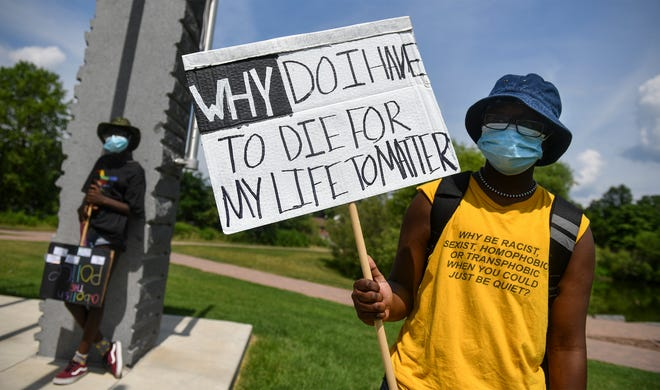Protest organizer Taban Gach holds a sign before marching Saturday, July 4, 2020, at Lake George in St. Cloud.