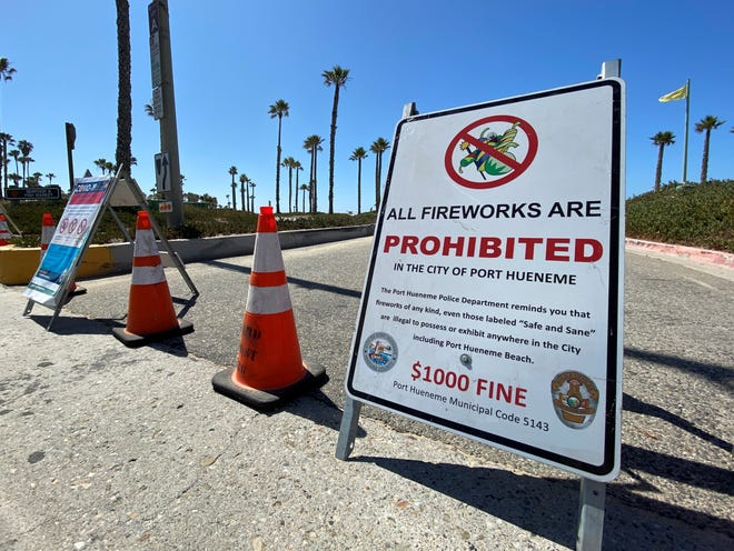 A no-fireworks sign stood near a coronavirus closure sign blocking a beach parking lot in Port Hueneme on July 3, 2020. Ventura County beaches were closed over the Fourth of July weekend after a recent spike in coronavirus cases.