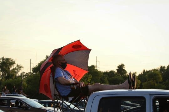 """Chris Hessek watches Rock Orchestra, a Delaware-based tribute organization, as they perform Beatles hits outside of Frawley Stadium as part of The Grands """"Concerts by Car"""" series during the coronavirus pandemic on Friday, July 3, 2020."""