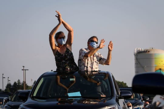 """Matt and Meryl Hewett dance out their sunroof to Rock Orchestra, a Delaware-based tribute organization, as they perform Beatles hits outside of Frawley Stadium as part of The Grands """"Concerts by Car"""" series during the coronavirus pandemic on Friday, July 3, 2020."""