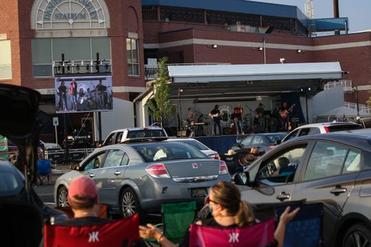 """A full parking lots jams to Rock Orchestra, a Delaware-based tribute organization, as they perform Beatles hits outside of Frawley Stadium as part of The Grands """"Concerts by Car"""" series during the coronavirus pandemic on Friday, July 3, 2020."""