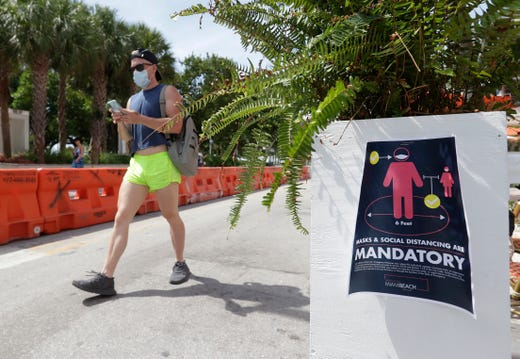A pedestrian, wearing a mask to prevent the spread of the new coronavirus, walks down Miami Beach, Florida's famed Ocean Drive on South Beach, July 4, 2020. The Fourth of July holiday weekend began Saturday with some sobering numbers in the Sunshine State: Florida logged a record number of people testing positive for the coronavirus.