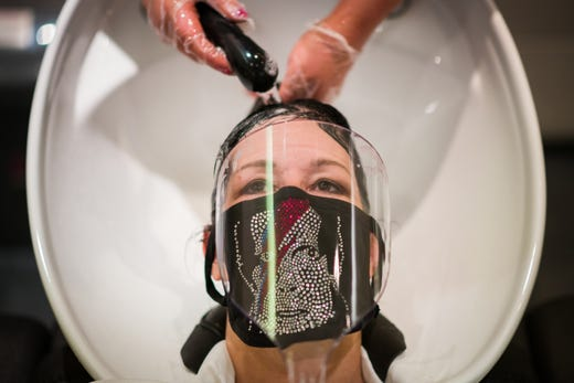 A customer has her hair washed at Tusk Hair stylists in Camden just after midnight on July 4, 2020 in London, England.
