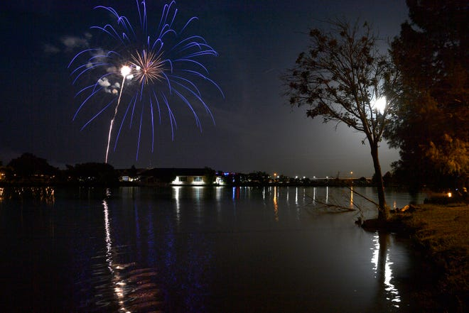 The full moon is silhouetted behind a tree on the shore of the lake at Nelson Park as fireworks are set off from behind the Abilene Zoo on Saturday.