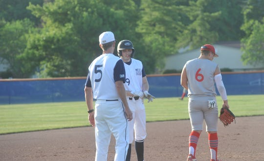 Bucyrus' Trevor Ley and Colonel Crawford coach Dan Gorbett chat between pitches.