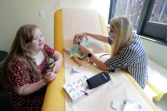 Emilyanne Wade, 12, left, looks on as Tricia Nora, a pediatric nurse practitioner, examines Sophia, Wade's baby doll June 17 in a medical clinic at Mary's Place, a family homeless shelter located inside an Amazon corporate building on the tech giant's Seattle campus.
