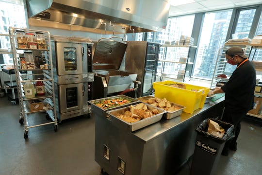 Joseph Robello, lead cook at Mary's Place, a family homeless shelter located inside an Amazon corporate building on the tech giant's Seattle campus, prepares food.
