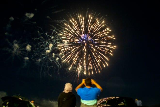 A family takes photos as fireworks explode during the Coralville 4th Fest drive-in fireworks show amid the novel coronavirus pandemic, Saturday, July 4, 2020, in Coralville, Iowa.