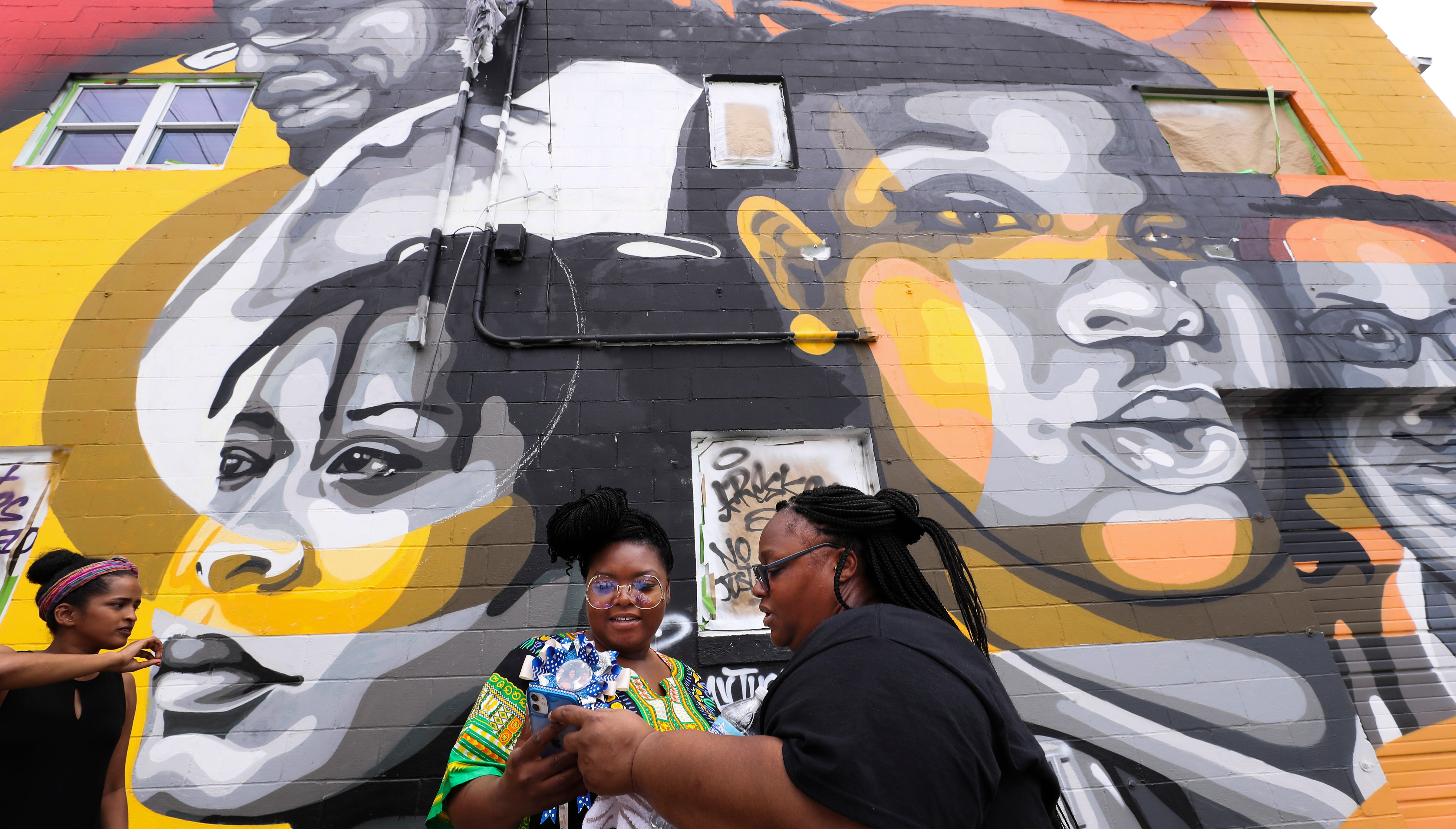 Tahasha Holloway, right, and her sister Bianca Austin looked at cell phone photos they shot as they attended the unveiling of a mural on West Main Street that prominently depicts their niece, Breonna Taylor, and other African Americans who have died at the hands of law enforcement on July 5, 2020.