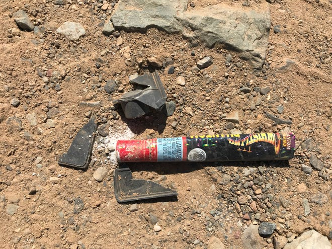 A spent firework was left in the dirt on a hill near where a fire burned into a ravine off Quartz Hill Road early Sunday morning.