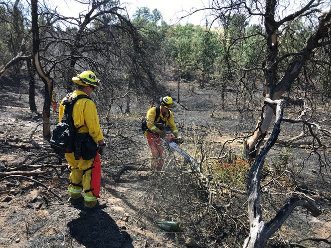 Redding Fire Department crews finish clearing brush in a fire that burned about 5 acres early Sunday morning off Quartz Hill Road near Stone Canyon Drive in northwest Redding.