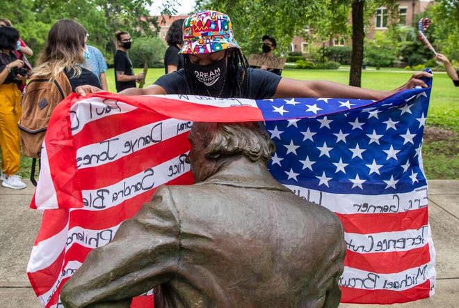 Marie Rattigan, 24, places an American flag over the statue of Francis Eppes, which is located on the Florida State University campus.