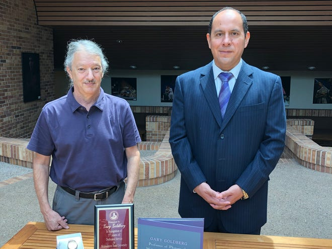 Dr, Martin Camacho, Dean of Fine Arts at Midwestern State University, presents retiring Professor of Art Gary Goldberg with a watch, plaque and book at a retirement event last week at MSU.
