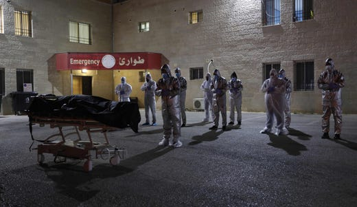 Palestinian health workers recite a prayer in front of the body of a woman who died after contracting the COVID-19 disease caused by the novel coronavirus, before her funeral in the West Bank city of Nablus on July 5, 2020.