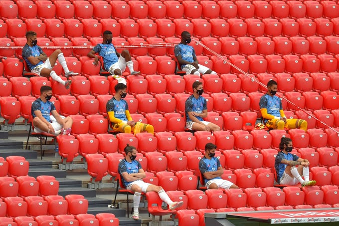 Real Madrid's substitute players wearing face masks sit in the stands during the Spanish League football match between Athletic Club Bilbao and Real Madrid at the San Mames stadium in Bilbao on July 5, 2020.