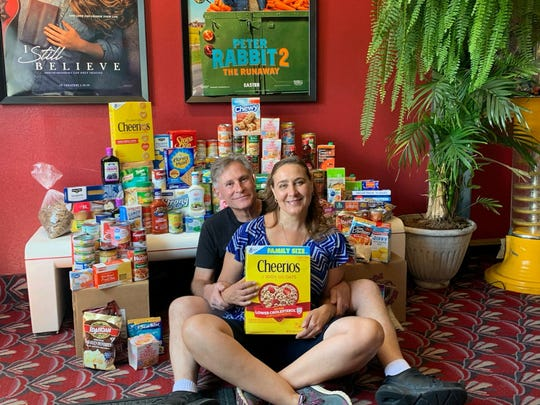 Bruce and Amber Gregory sort through food items at the Cinema Saver theater in Endicott. They own the theater and have been collecting food there for CHOW since March.