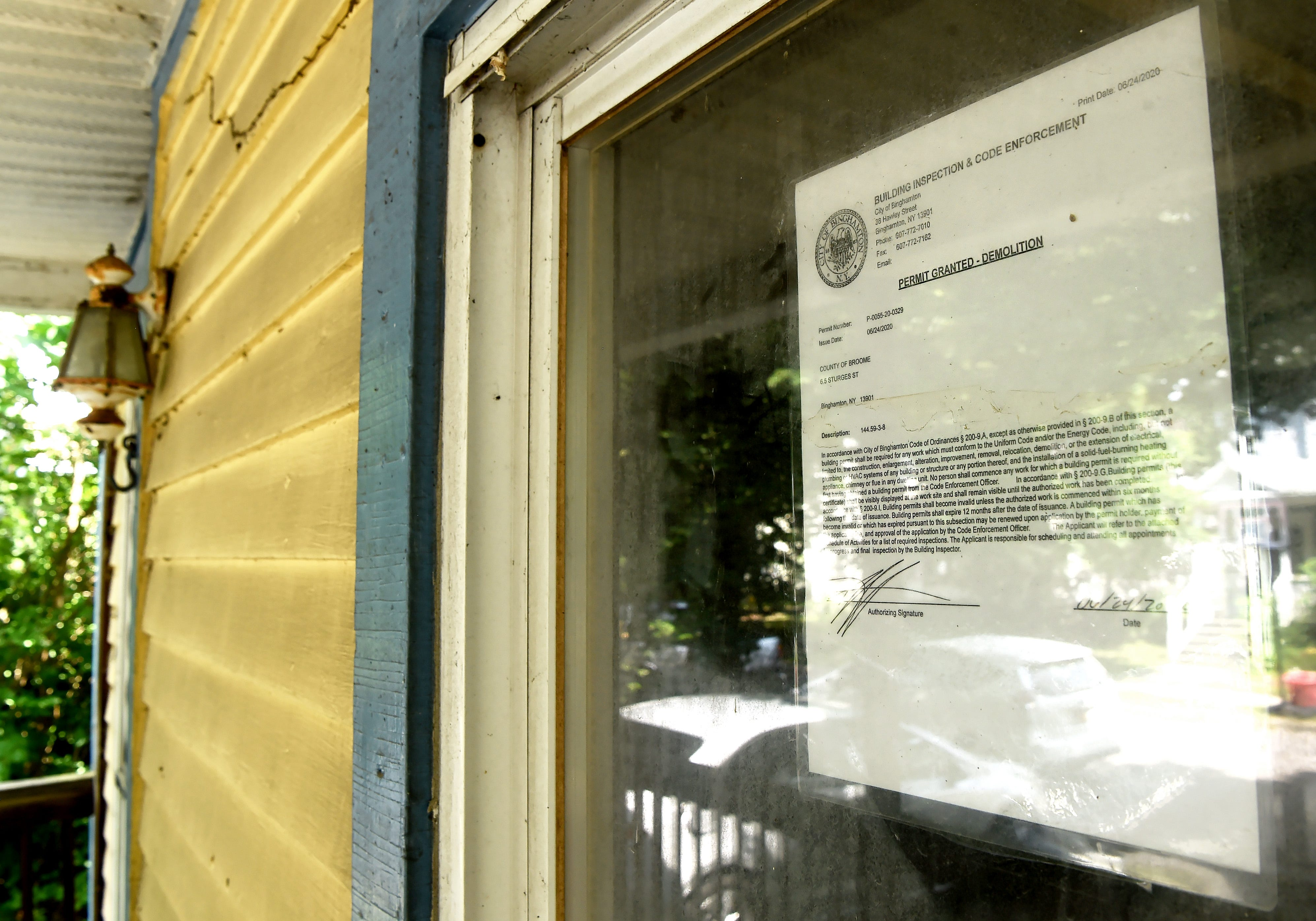 A demolition permit is affixed in a window at at 6 1/2 Sturges St. in Binghamton on July 2, 2020.