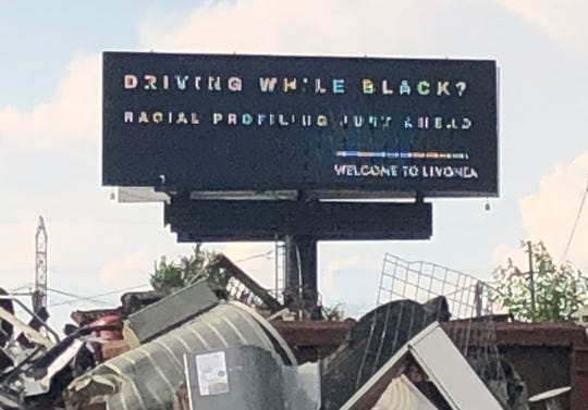 A digital billboard on Interstate 96 near Livonia says: 'Driving While Black? Racial profiling just ahead', with the tagline 'Welcome to Livonia.'