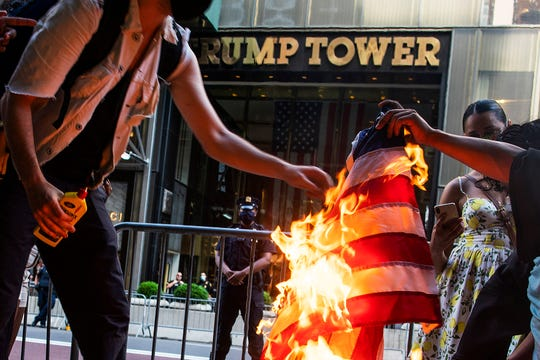 Protesters burn American flags during a protest in front of Trump Tower, Saturday, July 4, 2020, in New York.