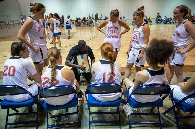 A coach instructs players during timeout of an AAU girls basketball game at the Indiana Convention Center, Indianapolis, Monday, July 6, 2020. When they're off the courts, players and fans are sent down opposite sides of aisles, plus hand sanitizer stations and cautionary signs are posted about the coronavirus.