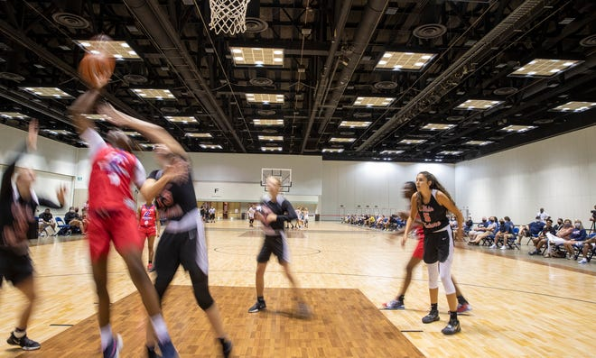 Players under the basket during an AAU girls basketball tournament at the Indiana Convention Center, Indianapolis, Monday, July 6, 2020. When they're off the courts, players and fans are sent down opposite sides of aisles, plus hand sanitizer stations and cautionary signs are posted about the coronavirus.