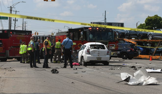 First-responders and accident investigators work at the scene of a crash near the intersection of South Martin Luther King Jr. Boulevard and West St. Joseph Street in Lansing on Monday, July 6, 2020.