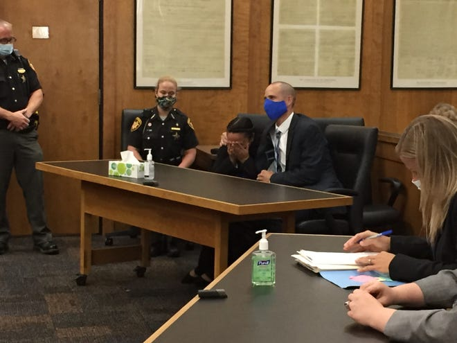 Jamie Haynes covers her eyes Monday afternoon after a jury found her not guilty of all three charges in connection with the death of her 14-day-old son. Defense attorney Sean Boone comforts his client.