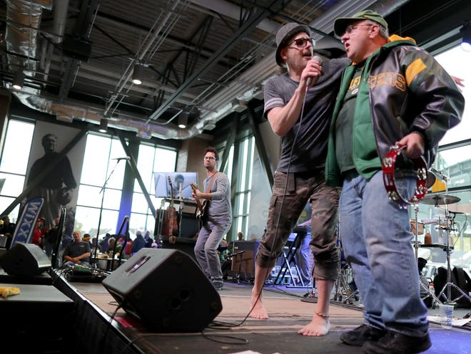 The Love Monkeys lead singer John Hauser brings Packers fan Arland Wingate on stage while playing before a Green Bay Packers game in 2018, at Lambeau Field in Green Bay. Hauser and The Love Monkeys will hold a concert with social distancing guidelines on July 10 at Okauchee Lions Park.