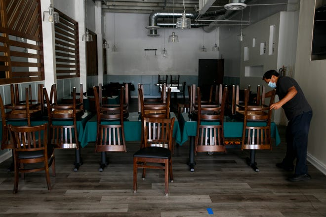 Fabian Nahui, the owner of a Peruvian restaurant, arranges chairs Monday, July 6, 2020, in Los Angeles. The coronavirus is blamed for over a half-million deaths worldwide, including more than 130,000 in the U.S., according to the tally kept by Johns Hopkins University.