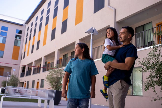 Reynaldo Galindo, 31, stands with his sons, Royall, 4, and Myson, 11, on July 6, 2020, at Urban Living on Fillmore in downtown Phoenix. Galindo and his children were living with friends before finding a three bedroom apartment at the new affordable housing project.