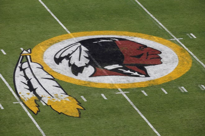 In this Aug. 7, 2014 file photo, the Washington Redskins NFL football team logo is seen on the field before an NFL football preseason game against the New England Patriots in Landover, Md. The recent national conversation about racism has renewed calls for the Washington Redskins to change their name.