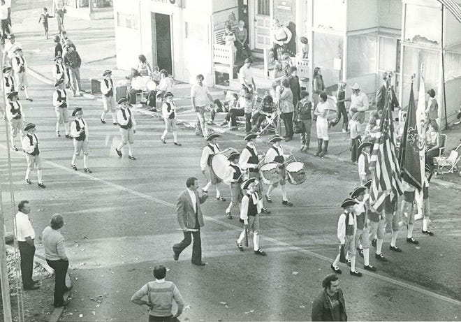 Director Ken Matthews walks with the North Hills Jr. High School Fife and Drum Corps during a parade in the 1970s.