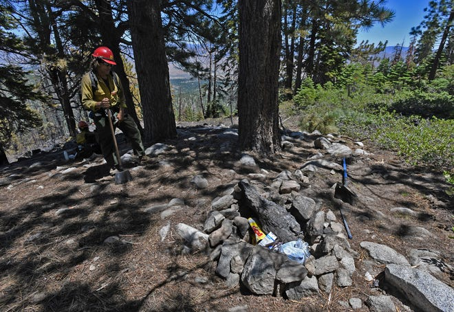 Dejon Clay, a firefighter with the U.S. Forest Service, stands next to a campfire pit where the Rose Fire is believed to have started on Slide Mountain Sunday afternoon.