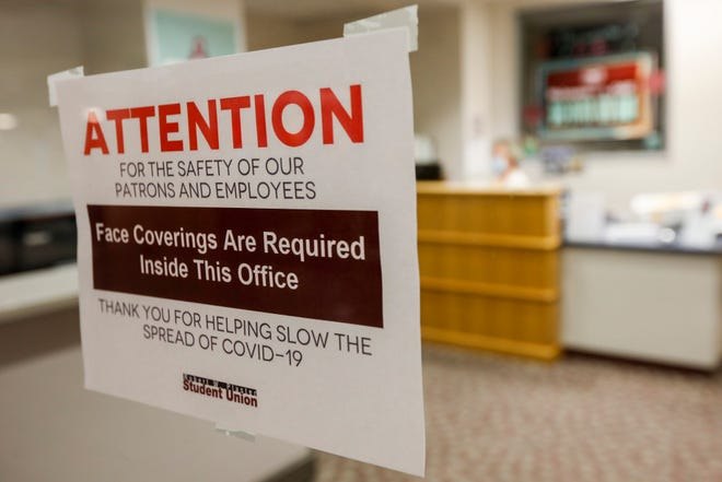A sign on the door of the student union at Missouri State University advises students that they are required to wear a face mask before entering the office.