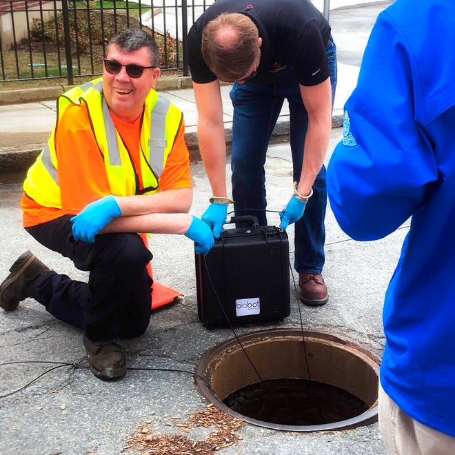 In this undated photo provided by Biobot in June 2020 technicians take a sewage sample. Across the U.S. and in Europe, researchers and health officials say they can track the course of a community outbreak by studying the waste flushed from its bathrooms. And that can provide a valuable addition to public health tools, they say. (Biobot via AP)