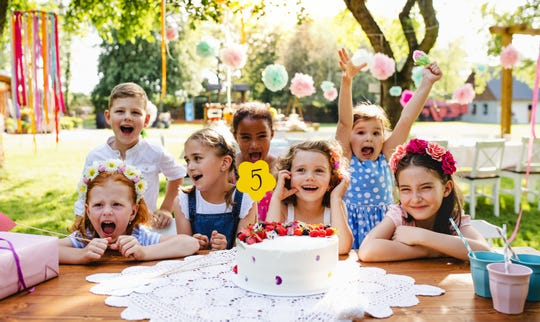 Children celebrate a five-year olds birthday with cake during birthday party.