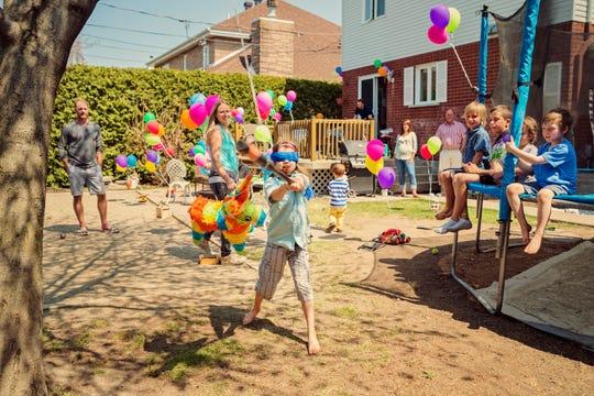 A young girl swings at a pinata at birthday party.