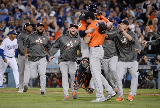 The Houston Astros celebrate while the Los Angeles Dodgers leave the field after Game  of the 2017 World Series.