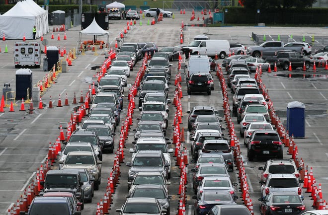 Drivers wait to be tested for COVID-19 at the Hard Rock Stadium parking lot July 6 in Miami Gardens, Fla. The state is experiencing a spike in  coronavirus cases and plans to close some businesses to combat the rise.