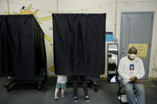Kat Wilson, center right, votes in a booth with her sons Asher, 3, and Colton, not visible, 1, at the Cruz Recreation Center in Philadelphia's Ludlow section on Pennsylvania's primary election day on June 2, 2020. There were fewer polling locations across the city due to the coronavirus pandemic.