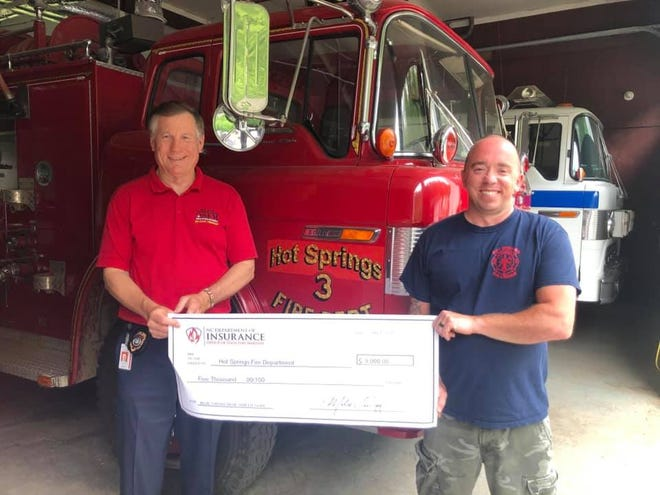 Hot Springs Fire Department Chief Josh Norton accepts a ceremonial check representing a $5,000 grant from the NC Department of Insurance Commissioner Mike Causey.
