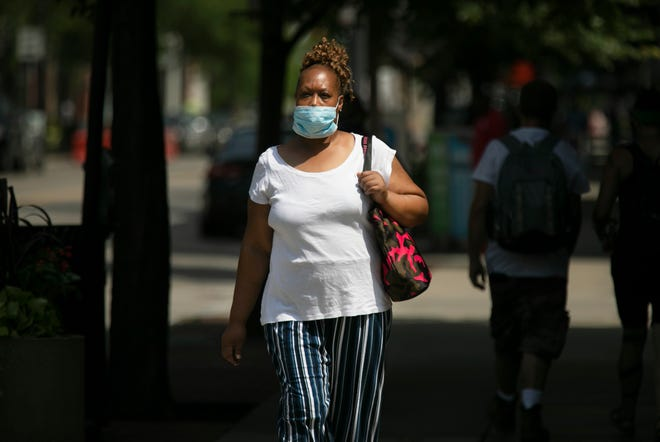 Rayonna Roach, of East Price Hill, walks down Vine Street in Over-the-Rhine, Tuesday, July 7, 2020. Though she said she agrees with the need to wear masks, she said it's sometimes hard to breathe. Cincinnati is now requiring masks be worn inside, effective July 9, 2020.