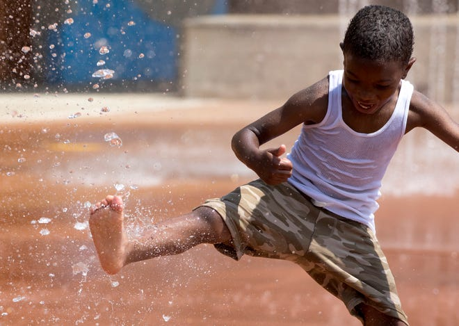 Ethan Scruggs, 6, kicks water at Armleder Memorial Spray Park in Cincinnati on July 7, 2020. According to the National Weather Service the high was near 95 with a Heat index values as high as 103. The spray park has a limit of 70 people to help prevent the spread of the new coronavirus.