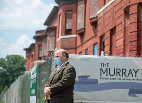 Detroit Mayor Mike Duggan listens to a press conference to announce the renovation of The Murray, a set of row homes in the Hubbard Farms neighborhood of Detroit, July 7, 2020.