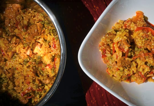 Chicken and sausage paella, with yellow and red peppers, is made with the medium-grain arborio rice. The paella was cooked in an Instant Pot.