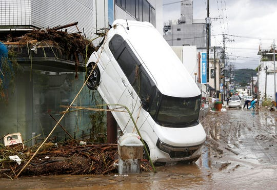 A car leans against a building following a heavy rain in Hitoyoshi, Kumamoto prefecture, southern Japan Monday, July 6, 2020.