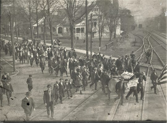 Marchers cross the tracks on Croghan Street in a 1918 parade.