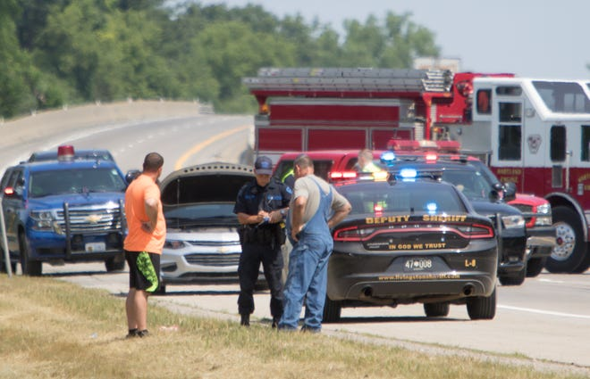 A Michigan State Police Trooper talks to a person on the shoulder of southbound U.S. 23,  the scene of a crash north of Crouse Road in Hartland Township Tuesday, July 7, 2020.