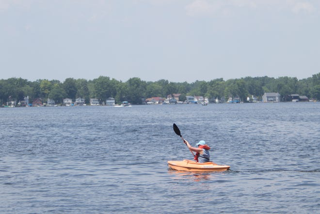 A kayaker paddles on Portage Lake Tuesday, July 7, 2020. The state issued an advisory not to eat fish from the lake and others connected to the Huron River.