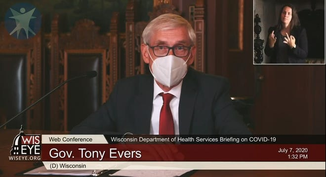 Gov. Tony Evers wears a face mask during a briefing with reporters on the state's response to the coronavirus pandemic.